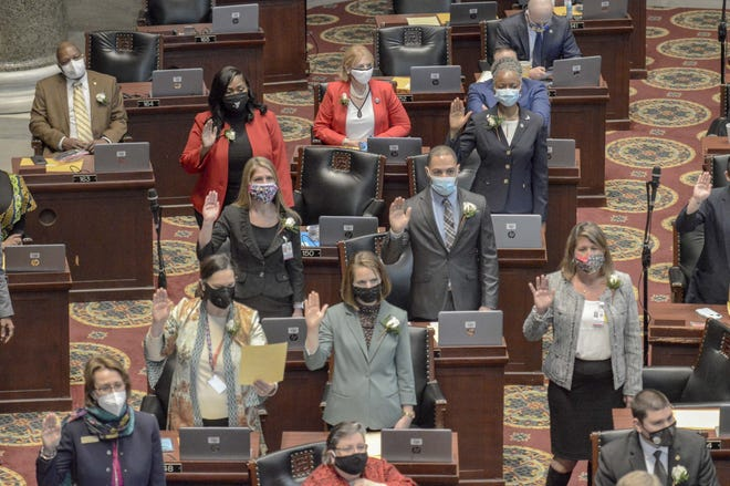 Members of Missouri's House of Representatives raise their hands as they're sworn in on the first day of the 2021 legislative session on Jan. 6.
