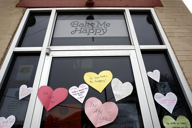 Supporters posted hearts over the doors and windows of Bake Me Happy after the Merion Village bakery closed early Sunday when it received racially charged threats of violence. The bakery reopened Tuesday.