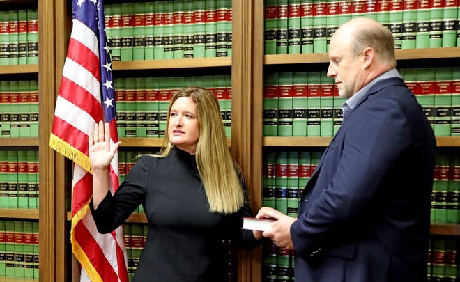 Lafourche District Attorney Kristine Russell takes the oath of office as her husband Blaine Russell looks on.