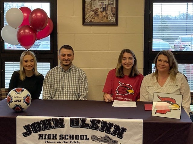 John Glenn senior Ashlynn Clack, (second from right) signed her National Letter of Intent to attend Wheeling University on Monday afternoon in the John Glenn High School library. Seated with Ashlynn are sister Taylor Clark, father Scottie Clark, and mother Jenelle Clark.
