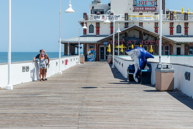 Visitors stop for selfie on an nearly empty Daytona Beach Pier last spring when things were closed due to the pandemic.