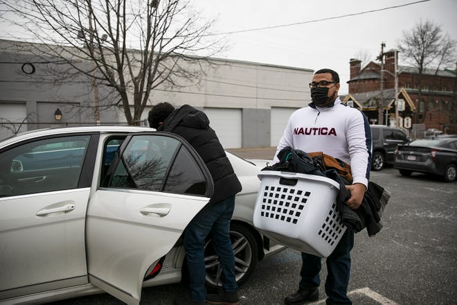 Brockton friends Maxwell Moukit, 23, and Jason Jenkins, 22, unload winter jackets they are donating to guests of the Old Colony Y Family Life Center in Brockton on Monday, Jan. 11, 2021. The two have donated over 300 jackets both new and lightly used.