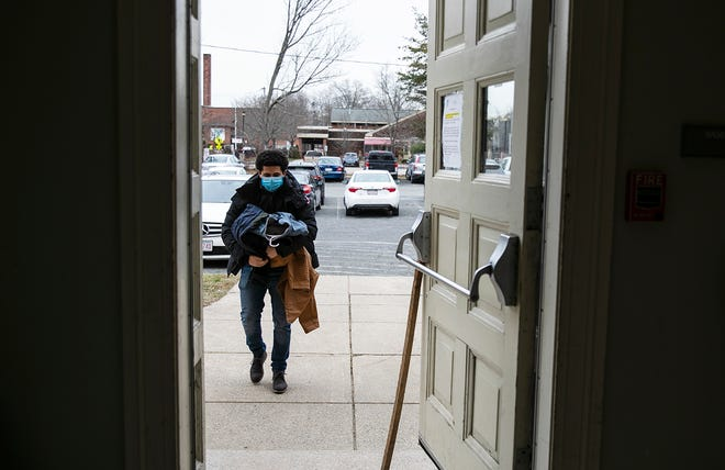 Maxwell Moukit, 23, of Brockton carries jackets for families at the Old Colony Y Family Life Center in Brockton on Monday, Jan. 11, 2021. Moukit and his friend Jason Jenkins, 22, have bought $2,000 worth of jackets to be donated to local shelters.
