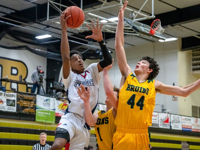 Truman senior Najee Williams, left, drives to the hoop against Columbia Rock Bridge defenders Kanyon Hummel (44) and Hudson Dercher (1) in the 810 Varsity Showcase Saturday at Lee's Summit High School. Williams poured in 30 points to lead the Patriots to a 68-50 rout of the Bruins.