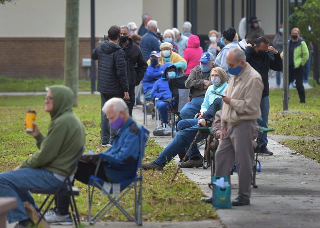 A line of Duval County residents snakes around the campus of the Mandarin Senior Center on Hartley Road on Monday, January 11, 2021, as they wait for COVID-19 vaccine injections at one of two new City of Jacksonville vaccine sites which opened Monday.