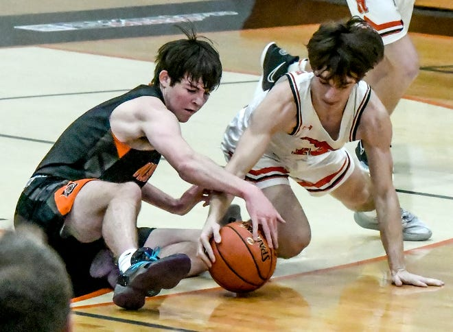 Holcomb's Dalton Long, right, and Ulysses' Lance Walker battle for control of a loose ball Friday at Holcomb. The Longhorns defeated the Tigers in overtime, 80-76.