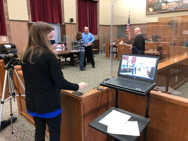 Ellis County Commissioner Dean Haselhorst, center, takes the oath of office Monday before his wife, Julie, holding the Bible, and 23rd Judicial District Chief Judge Glenn Braun, right, as court administrator Amanda Truan livestreams the ceremony from the Ellis County Courthouse.