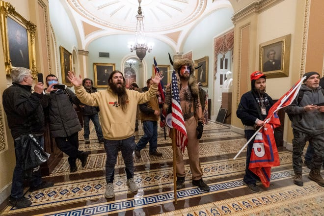 In this Jan. 6, 2021 file photo, supporters of President Donald Trump are confronted by U.S. Capitol Police officers outside the Senate Chamber inside the Capitol in Washington. Jacob Anthony Chansley, the Arizona man with the painted face and wearing a horned, fur hat, was taken into custody Jan. 9, 2021 and charged with counts that include violent entry and disorderly conduct on Capitol grounds. (AP Photo/Manuel Balce Ceneta, file)