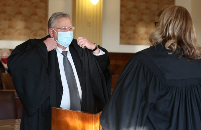 Keith Schroeder puts on his robe before being sworn in as District Court Judge by Chief Judge Patty Macke Dick Monday morning at the Reno County Courthouse. Schroeder was the former Reno County District Attorney and replaces retired Judge Tim Chambers.