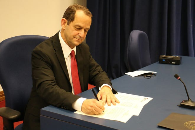 NC Sen. Michael Lazzara signs papers after being sworn into office for the North Carolina Senate District 6 seat following taking oath of office during the Jan. 2 virtual ceremony.