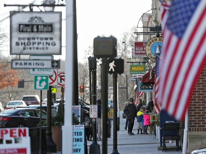 A family walks past businesses on Main Street in Hudson on Saturday. The city is looking at ways to draw people downtown to help businesses during the winter as the COVID-19 pandemic continues.