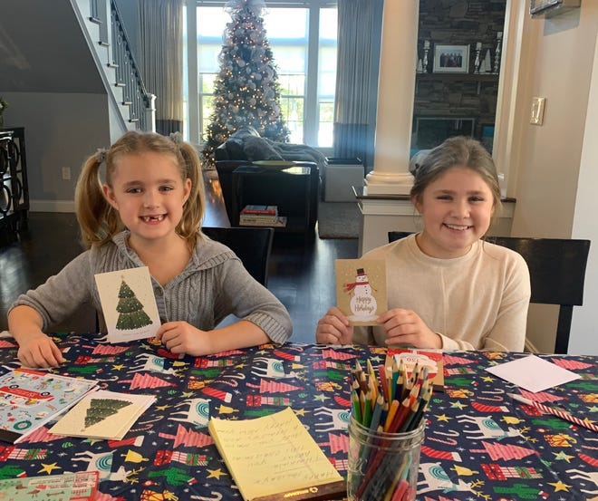 Congresswoman Lori Trahan's daughters write out cards of their own for Montachusett Home Care Corporation's Cards for Caring initiative.