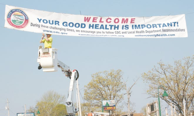 A sign is raised on the Bagnell Dam Strip during the start of the COVID pandemic, welcoming guests and promoting good health.