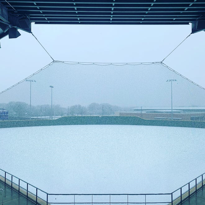 Snow continues to fall as Midlothian High School's softball field is covered in white on Sunday. Schools in Ellis County returned to classes on Monday on a two-hour delay. By midweek, the wintry precipitation was to be but a pleasant memory as temperatures return to the 50s and 60s.