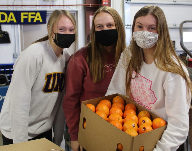 Nevada High School agriculture education students and FFA members hold a box of navel oranges: left to right, Sydney Mosinski, Aubrey Gibson and Katelyn Kingsbury.