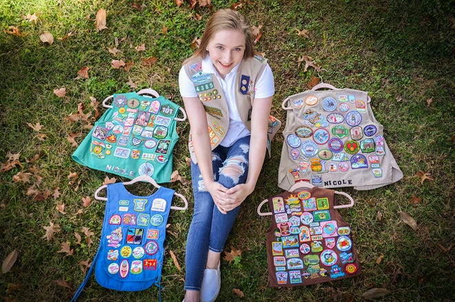 Nicole Cope shows off her many badges she has earned while being a Girl Scout