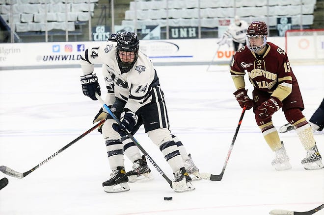 UNH's Tyler Ward, left, shields the puck from Boston College's Nikita Nesterenko during Sunday's Hockey East game at the Whittemore Center. Boston College won 3-2 in overtime.