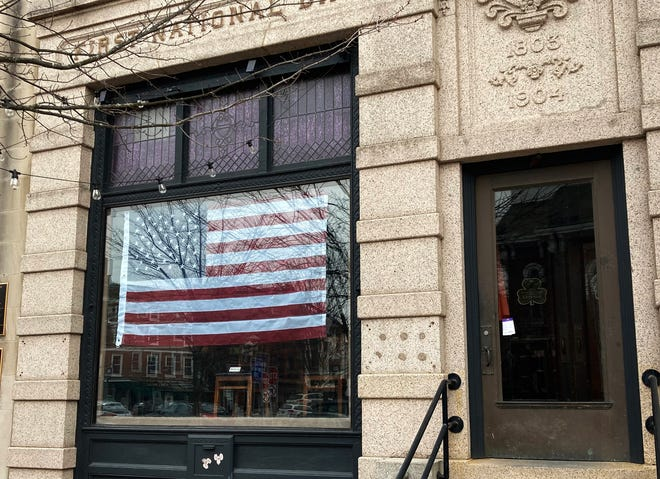 United States flags hang Monday, Jan. 11, 2021 in the windows of the restaurant formerly known as Ri Ra in Portsmouth's Market Square. The space will become a barbecue eatery called Portsmouth Feed Company.