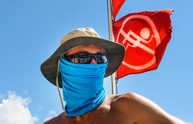 Palm Beach lifeguard George Klein wears a mask at Midtown Beach in Palm Beach that remains closed due to red tide warnings, Sunday, September 30, 2018. (Melanie Bell / The Palm Beach Post)