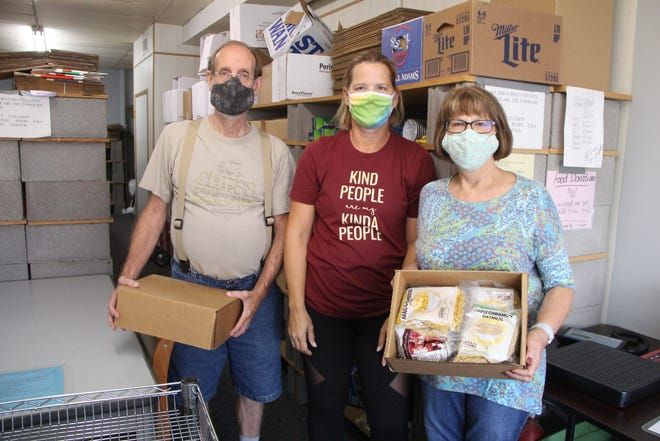 Lyle Taylor (from left), Susan Pixler and Diana Harris organize food donations for distribution to those needing help in Pratt County at the Pratt County Food Bank.