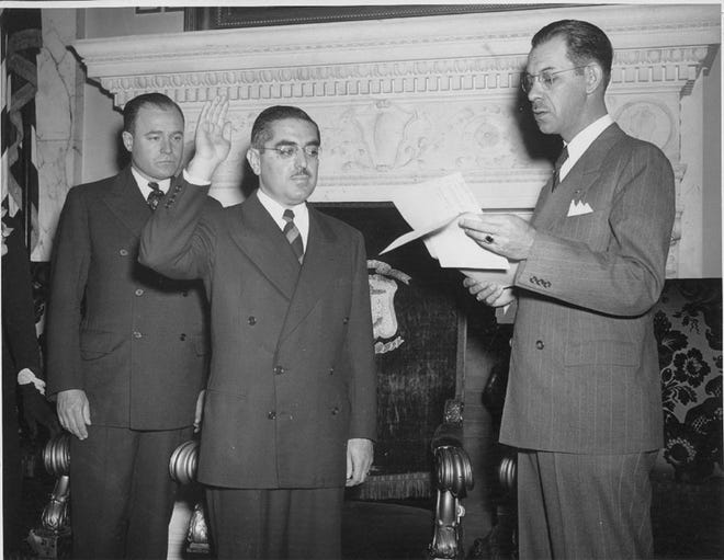 Former Gov. J. Howard McGrath, left, looks on as new Gov. John O. Pastore, center, is sworn in by Secretary of State Armand Cote, in October 1945.