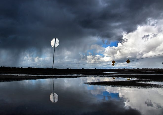 Storm clouds are reflected in a puddle as they approach Undine Road and Wing Levee Road in French Camp.