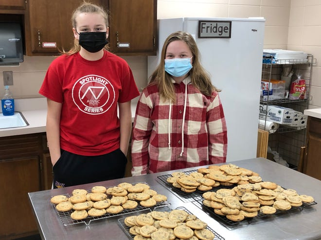 Alynn Solberg and Amber Taylor pose with the cookies they baked and donated.