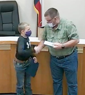 Stephenville Mayor Doug Svien, right, presents a Certificate of Recognition to Kason Prince in this video still from the Jan. 5 Stephenville City Council meeting. Prince has raised more than $36,000 for the Backpack Buddies of Erath County program, which provides meals to food-insecure youth so they don't go hungry over the weekend or when school is not in session.