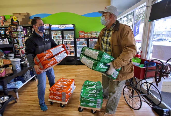 From left. Fred Harrill and Larry Smith load up dog food to be donated to Friends of Cleveland County Animals at RollOver Pets on Monday.