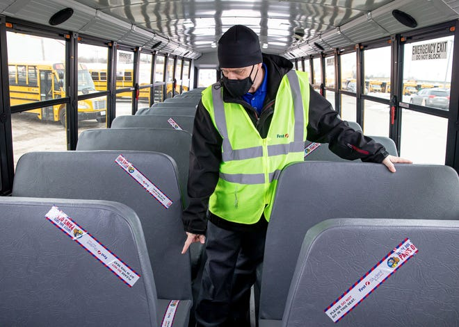 Josh Goosen, senior location manager for First Student, shows the tape covering seats on the school bus that keeps students socially distanced from the drivers as First Student unveils one of the new buses, Monday, January 11, 2021, in Springfield, Ill. First Student will be replacing 76 of the approximately 200 buses that serve District 186 that will be outfitted with advanced tablet technology and audio programming that allows drivers to access important information, including the fastest routes. The buses will also have WiFi camera systems with FirstView technology that enables parents to track their child's bus and FirstACTS a web-based communication tool that helps efficiently track student conduct on school buses. [Justin L. Fowler/The State Journal-Register]