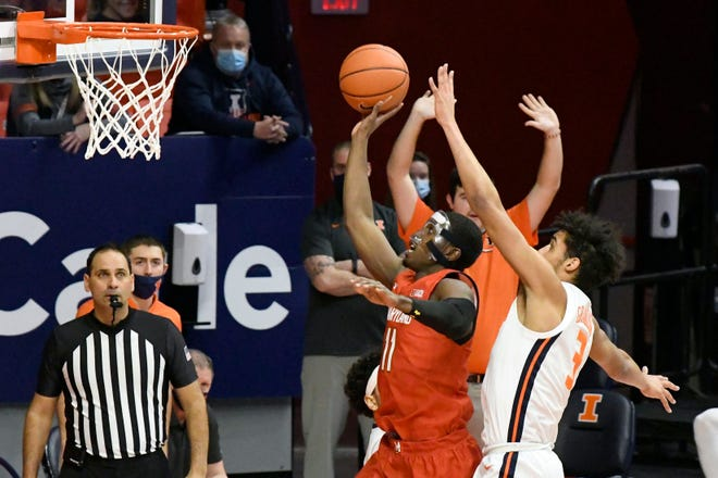 Maryland guard Darryl Morsell shoots against Illinois guard Jacob Grandison in the first half Sunday in Champaign. [HOLLY HART/THE ASSOCIATED PRESS]