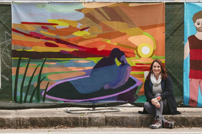 Artist Dana Richardson with her canvas on the construction fencing on Drayton near Bolton Street. Richardson's work is a part of the Starland Mural Project Fence Art.