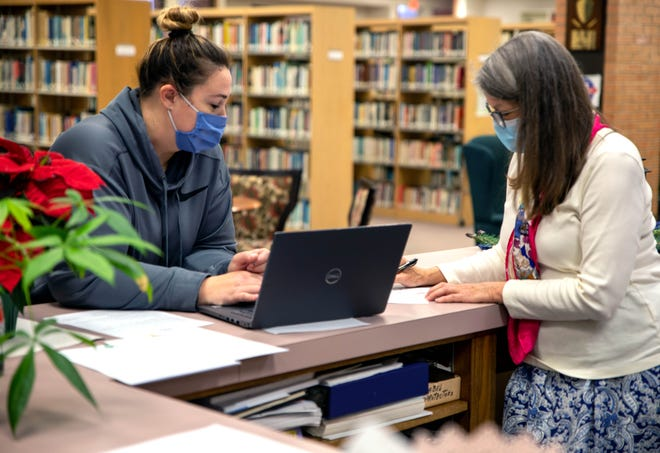 SSC Student Lacy Fisher (left) is assisted by Librarian Robin Tyler (right) for a laptop loan process in the Boren Library.
