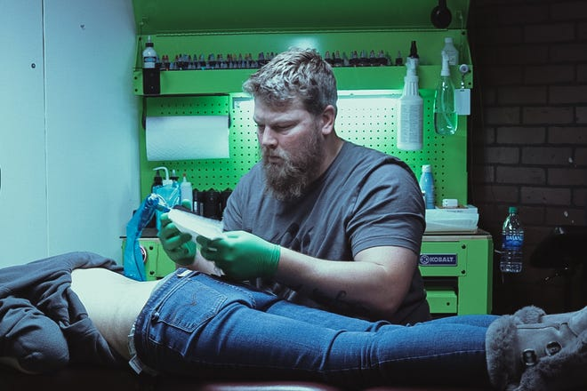 Tattoo artist and owner of Squid Ink tattoo shop Jason Baker is pictured giving a tattoo to a client in his new shop in Shawnee.
