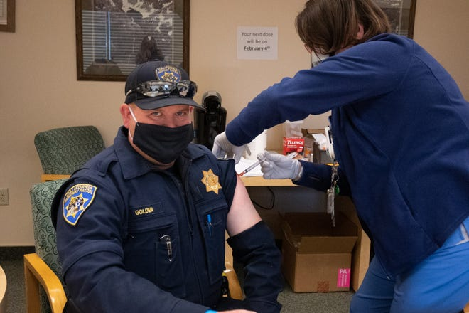 California Highway Patrol Officer John Golden receives his first dose of the vaccine from Fairchild Medical Center RN Ann-Marie Moser last week in Yreka.