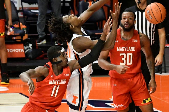 Illinois guard Ayo Dosunmu (11) is fouled by Maryland's guard Darryl Morsell (11) as he goes to the basket in the first half of an NCAA college basketball game Sunday, Jan. 10, 2021, in Champaign, Ill. (AP Photo/Holly Hart)