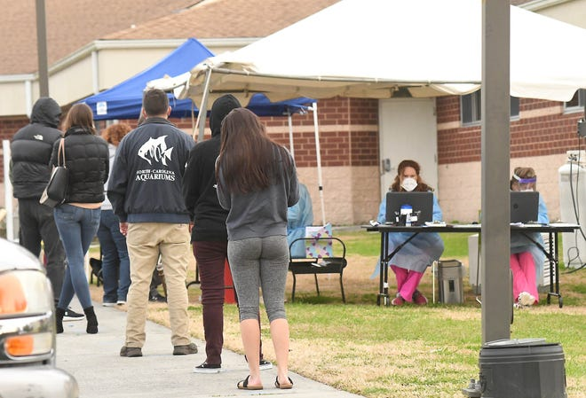 People wait in line to be tested for COVID-19 outside of the MedNorth Health Center on North 4th Street in Wilmington Thursday Jan. 7, 2021.