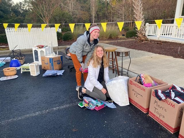 Laney's Gracyn Dwyer (left) and Isabella Bufalini take time for a photo during the Project Run Yard Sale Saturday. The Laney duo started Project Run as a club to benefit the Wilmington running community.