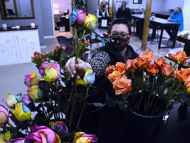 Michelle Jette-Pendleton of Griswold arranges rainbow roses during her grand opening of Everly After Floral Monday in the Stockhouse Building behind the Baltic Fire Department. [John Shishmanian/ NorwichBulletin.com]