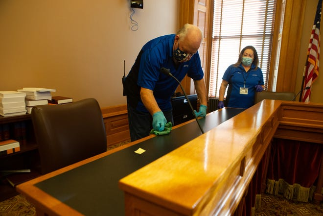 Kansas Statehouse custodial staff work to sanitize surfaces in a committee room on Dec. 11 prior to the start of the 2021 legislative session. Staff in the capitol have been affected by the unique conditions of this year's session due to COVID-19. (Evert Nelson/The Capital-Journal)