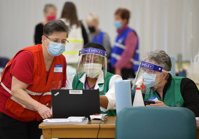Workers at a vaccination station at the Worcester Senior Center earlier this month.