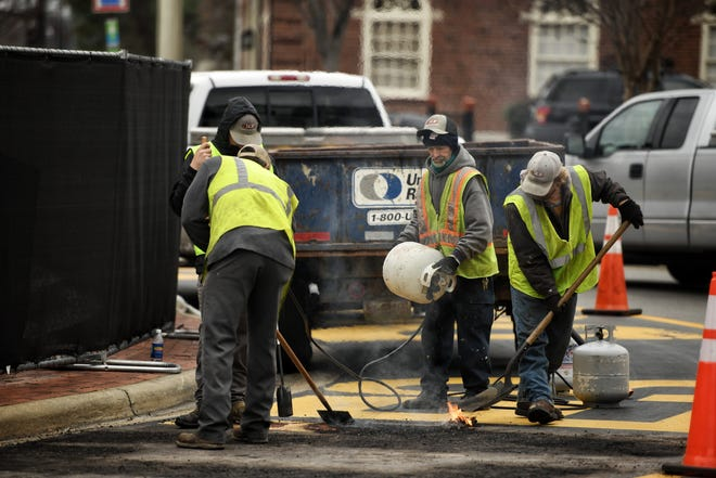 City crews remove the slogans on the traffic circle around the Market House on Monday, Jan. 11, 2020
