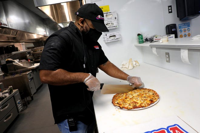 Manager Nick Johnson slices a pizza at the new Pizza Cottage at 8753 Owenfield Drive in Lewis Center.