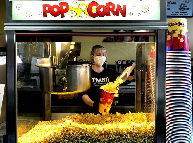 Strand Theatre employee Vaughn Duncan, a Delaware resident and Ohio Wesleyan University student, serves some popcorn during a Bring Your Own Movie showing at the cinema, 28 E. Winter St. in Delaware.