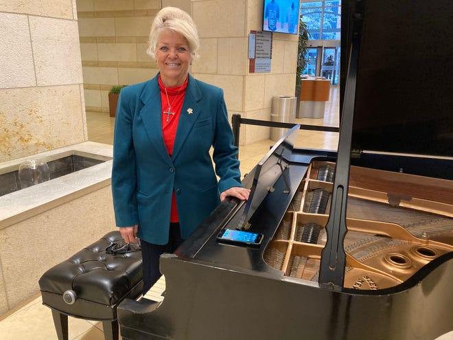 Susan Rodriguez stands at the piano she plays prior to church service every Sunday morning at FBC downtown Dallas.