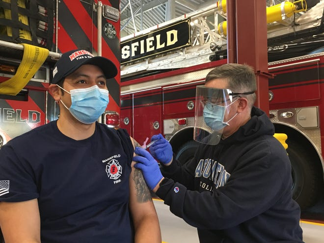 Canton first responders will be vaccinated at the fire station this week. Here, Mansfield firefighter Edgar Kaplan-Vigil is the first member of the Mansfield Fire Department to receive a COVID vaccination Sunday, Jan. 10 at the Mansfield public safety building. Mansfield Fire Capt. Marc Goyette administered the vaccines.