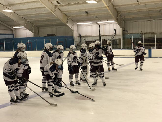 The Belmont Girls Varsity players bang their sticks on the ice, a social distancing replacement for handshakes, after a 4-2 victory over Lexington in their season opener at the Skip Viglirolo Rink.  Belmont's captains are Seniors Del Bonnin, Sam Rocci, Kendall Whalen, and Emma O'Donovan.