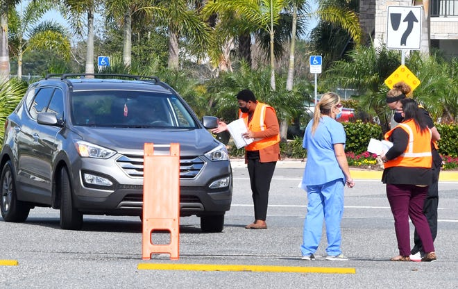 Florida Department of Health-Brevard staff check in people recently at the drive-thru COVID-19 vaccination site in Viera.