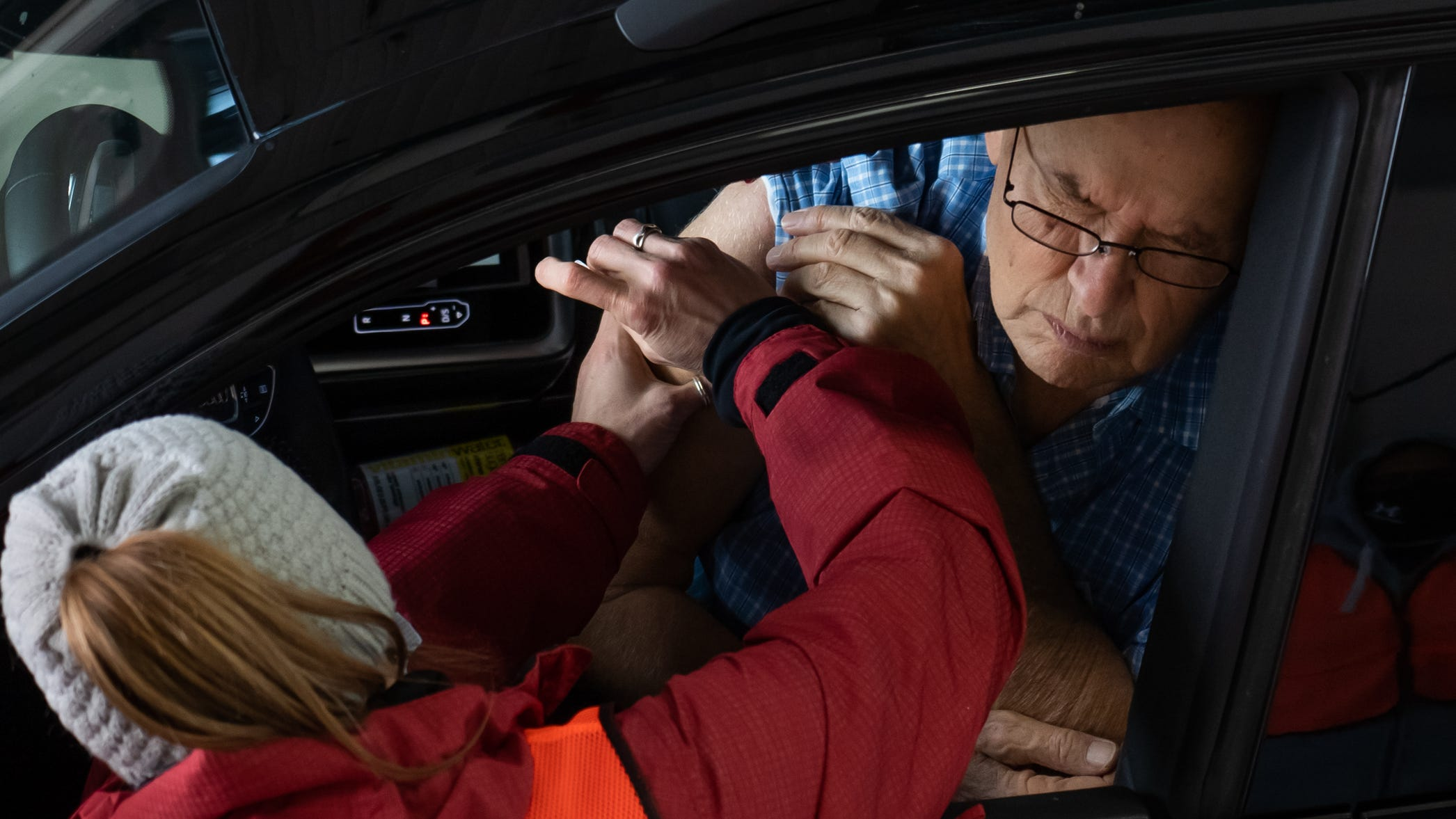 Frank Barbat of Waterford responds by being inoculated with the Pfizer COVID-19 vaccine by Oakland County Health Division RN Julie Traicoff during a drive-by vaccination at the Regional Fire Department of the Township of Waterford on Monday, January 11, 2021.