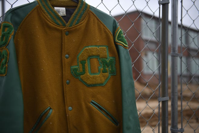 A football letterman jacket from Jackson Central-Merry High School hangs from the fence around the construction work going on at the school now. Athletic teams at the school will return when classes resume in the fall after a five-year hiatus.